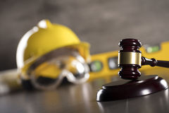Construction law. Law theme. Construction law`s symbols  - helmet and gavel. Stone table Stock Photos