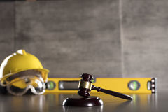 Construction law. Law theme. Construction law`s symbols - helmet and gavel. Stone table Royalty Free Stock Image