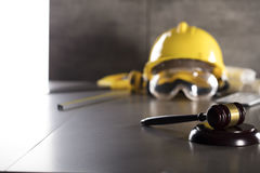 Construction law. Law theme. Construction law`s symbols  - helmet and gavel. Stone table Royalty Free Stock Images