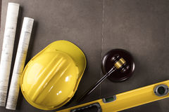 Construction law. Law theme. Construction law`s symbols - helmet and gavel. Stone table royalty free stock photography