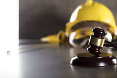 Construction law. Law theme. Construction law`s symbols - helmet and gavel. Stone table Stock Image
