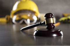 Construction law. Law theme. Construction law`s symbols - helmet and gavel. Stone table Stock Images