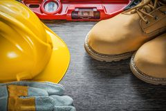 Construction level building helmet protective gloves boots on wo Stock Photo