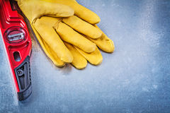 Construction level protective gloves on scratched metallic backg Royalty Free Stock Photography