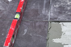 Construction level tiling at home tile floor adhesive Stock Image