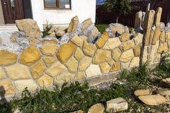 Construction of limestone fence near residential house. Stone ma Stock Photos