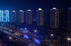 Construction lumineuse de gratte-ciel dans une rangée et une autoroute par nuit, Shenyang, Chine images libres de droits