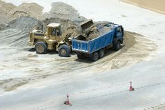 Construction Machineries. A dump truck being filled-up with graver by the bulldozer Stock Image