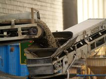 Construction machinery. A front end loading machine spraying gravel from a mixer truck Stock Photography