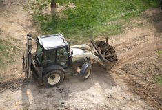 Construction machinery carries pieces of asphalt for loading. Road construction machinery in bucket carries pieces of old asphalt for loading Royalty Free Stock Images