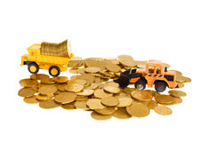 Construction machinery and coins Royalty Free Stock Images