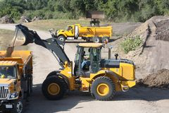 Construction Machinery. Yellow end loader and dump trucks working at a pile of dirt Royalty Free Stock Photography