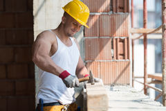 Construction Man Hitting Wood With Hammer Stock Photo