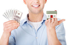 Construction man holding house model and money Stock Photos
