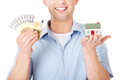 Construction man holding house model and money Stock Photography