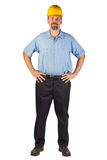 Construction Man Standing and Ready at an Angle. A blue collar worker standing, facing at an angle, strong with hands on hips. This man could be a technician Royalty Free Stock Image