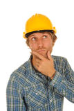 Construction man thinking. Handsome construction man wearing a yellow hardhat thinking Royalty Free Stock Photo