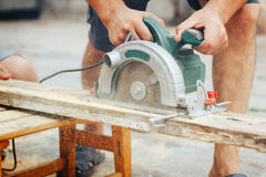 Construction man working with a chop saw in wood workshop. Details of wood cutting using circular saw. A man using a circular saw to cut the wood royalty free stock image