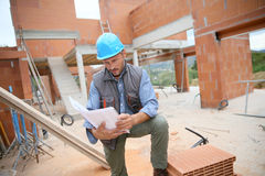 Construction manager analysing blueprint Stock Images