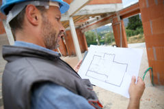 Construction manager analysing blueprint Stock Photos