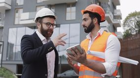 Construction manager and architect man are discussing the construction plan of the modern business center. They checks