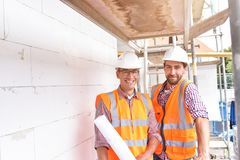 Construction manager and architect on site during the construction of a house - planning and control on site - teamwork stock photography