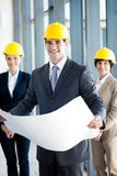 Construction manager & colleagues. Young construction manager holding blue print in front of colleagues royalty free stock image