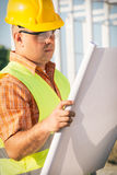 Construction manager controlling building site with plan Stock Photos