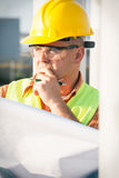 Construction manager controlling building site with plan Royalty Free Stock Images