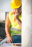 Construction manager controlling building site with plan Royalty Free Stock Photography