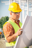 Construction manager controlling building site with plan Royalty Free Stock Image