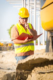 Construction manager controlling building site with plan. On construction site royalty free stock images