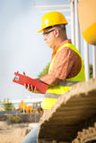 Construction manager controlling building site with plan Stock Photo