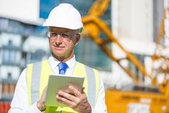 Construction manager controlling building site and tablet device in his hands Royalty Free Stock Image