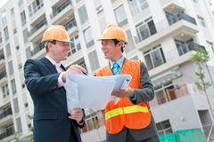 Construction manager and engineer. Discussing blueprint of the building Stock Photography