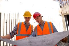 Construction manager and engineer dressed in work clothes and hard hats explore project documentation on the building stock photography