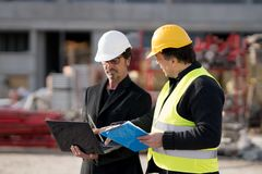 Construction manager and engineer at work on construction site. Civil engineer giving instructions to a construction worker using a computer laptop. Outdoors Stock Photography