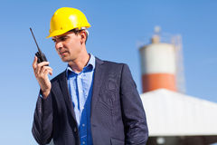Construction manager. Handsome construction manager using walkie talkie outdoors Stock Images