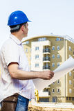 Construction manager holding project. And observed on building site Stock Photos