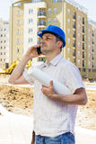 Construction manager holding project. And speaking by phone on building site Stock Photo
