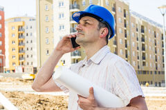 Construction manager holding project. And speaking by phone on building site Royalty Free Stock Photo