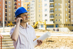 Construction manager holding project. And speaking by phone on building site Royalty Free Stock Image