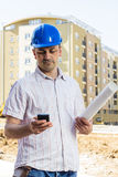 Construction manager holding project. And using phone on building site Royalty Free Stock Photo
