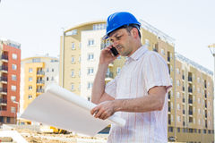 Construction manager looking project. And speaking by phone on building site Royalty Free Stock Images