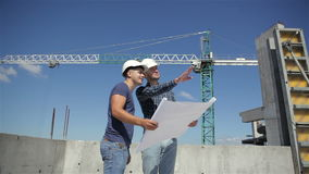 Construction manager points at the plan of building under construction stock video