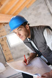Construction manager on site analysing blueprint Stock Image