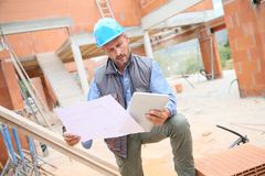 Construction manager on site with blueprint Stock Image