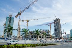 Construction of many modern high rise buildings with large cranes at sea side of capital Luanda, Angola, Southern Africa. Construction of many high rise Stock Image