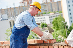 Construction mason worker bricklayer. Bricklaying construction worker. Mason bricklayer installing red brick with trowel putty knife Stock Photos
