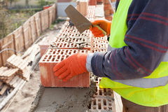 Construction mason worker bricklayer installing red brick with Royalty Free Stock Images